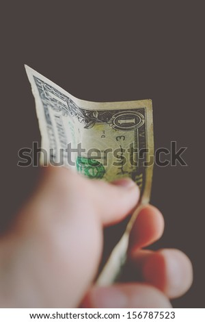 One dollar in hand. Small depth of field. - stock photo