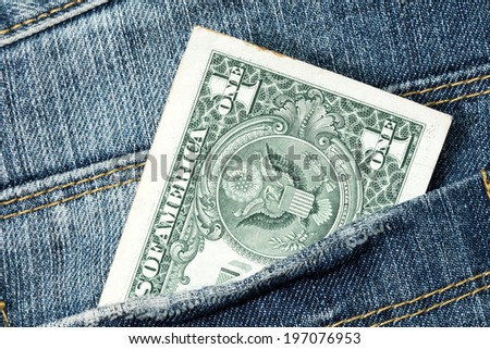One dollar note in the back pocket of denim trousers  - stock photo