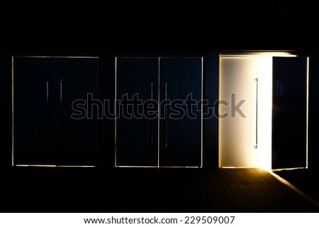 One door opened and light coming through the space mean hope or Exit of life - stock photo