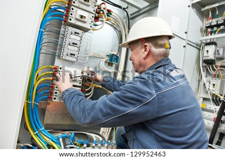 One electrician at work with wrench spanner tighten the screw in electical box - stock photo