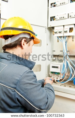 One electrician builder at work installing energy saving meter into electric line distribution fuseboard - stock photo