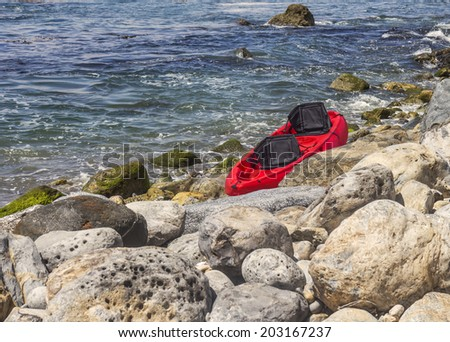 One empty bright red kayak with black seats waiting on rocky shore. Big boulders, green moss covered rocks, blue water.  - stock photo
