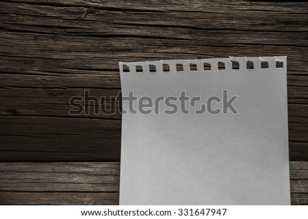 one empty page of notebook and on wooden table background. Natural material texture. Empty space for inscription or objects. Dark dramatic light.    - stock photo