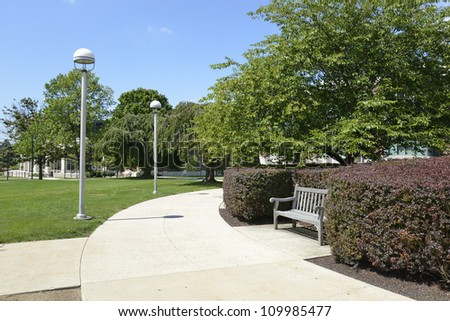 one empty wood bench by a concrete sidewalk and landscaped - stock photo