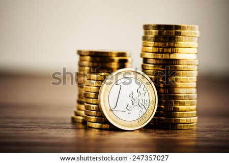 one euro coin and gold money on the desk - stock photo