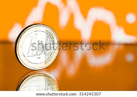 One euro coin. Fluctuating graph on yellow background. Rate of the euro  (shallow DOF)  - stock photo