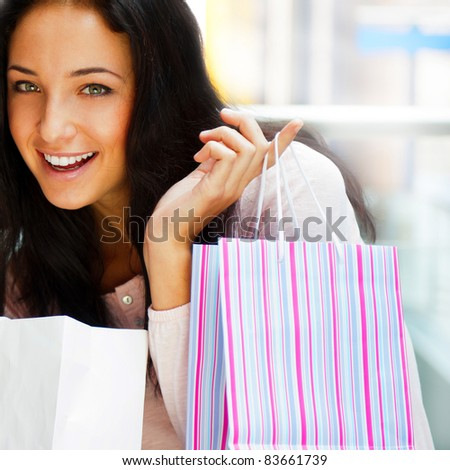One excited shopping woman resting on bench at shopping mall looking at camera - stock photo