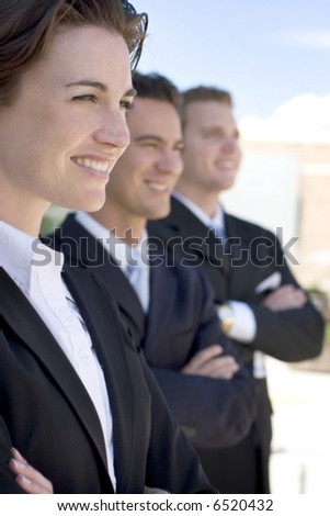 one female two males wearing dark business suits in a row smiling - stock photo