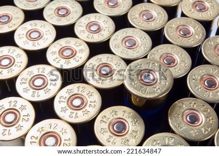 One fired shotgun shell among unused ammo - stock photo