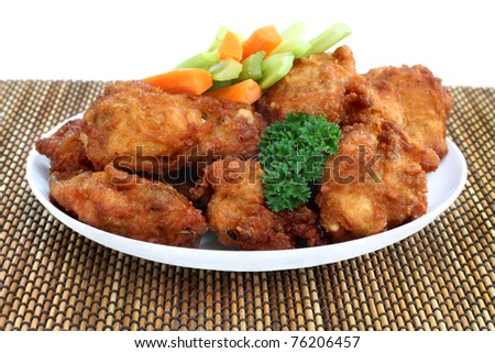 One full plate of crisp and fresh chicken wings with celery and carrots and a parsley garnish. - stock photo