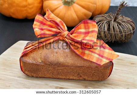 One generic pound cake wrapped in a fall ribbon - idea for a hostess gift. - stock photo