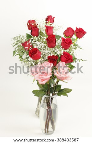 One glass vase bouquet of pink roses  in front of a glass vase of red rose s floral arrangement in front of an off white background. Two pretty rose bouquets in glass vases. - stock photo