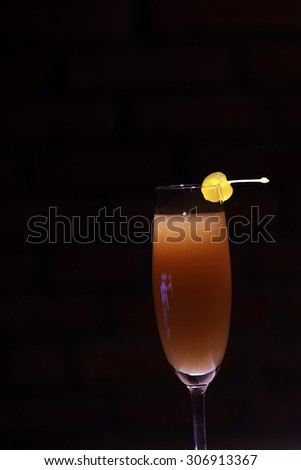 One glass with alcoholic mimosa or valencia cocktail of apricot liqueur orange juice sparkling dry wine and yellow cherry with stem on brick wall background, vertical photo - stock photo