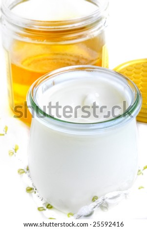 one glass with yoghurt and one glass with honey on a table - stock photo