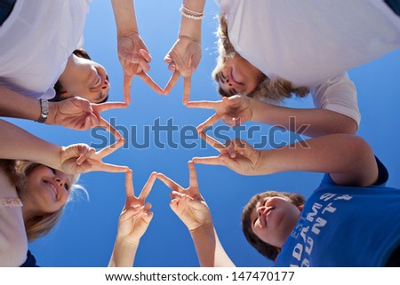 One good successful team of young teenage children forming a star with their fingers touching to the form the points against a clear blue sky, conceptual of cooperation and teamwork - stock photo