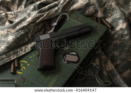 one gun colt on khaki clothing military uniforms with sleeves for the arms box - stock photo