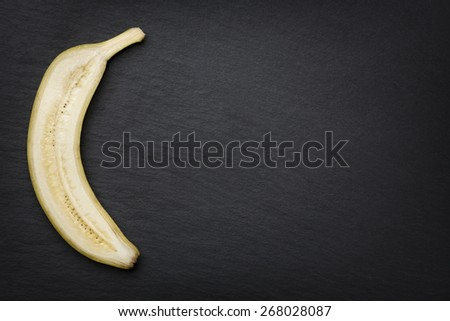 One half of a sliced banana, looking noble, isolated on dark stone slab with empty copyspace. - stock photo
