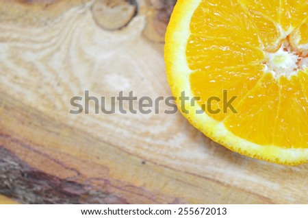 One half of an orange close up on a plank - stock photo