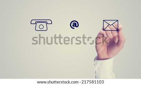 One Hand Making Web Graphic Elements of Phone, At Sign and Envelope, Isolated on Gray Sky Background. - stock photo