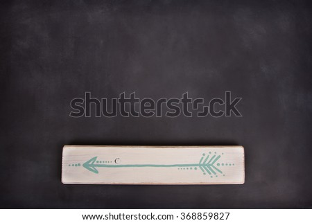 One hand painted arrow on a wooden plank on a blackboard background - stock photo