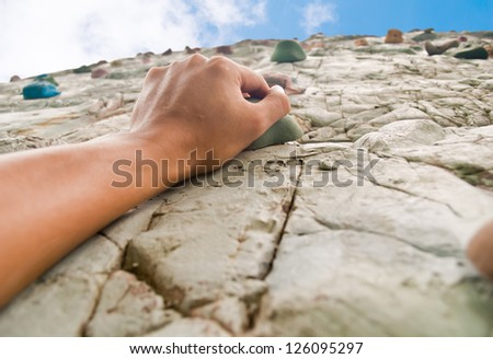 One hand to climb the cliff(Sport Climbing) - stock photo