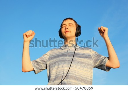 one handsome man is listening music outdoors with closed eyes. - stock photo