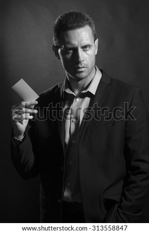 One handsome sexy unshaven young guy in jacket and shirt holding business card in hand looking forward standing on studio background black and white copyspace, vertical picture - stock photo