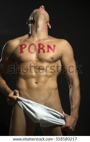 One handsome stripped muscular man in white underwear with beautiful sexy body with text of porn written by red lipstick standing with trown back head in studio on black background, vertical picture - stock photo