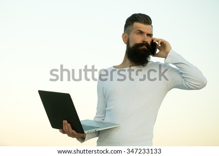 One handsome young bearded business man in white sweater holding and working on laptop talking on mobile phone outdoor on light sky natural background, horizontal picture - stock photo