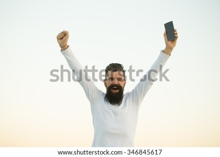 One handsome young bearded emotional business man in white sweater holding cell phone outdoor on light sky natural background, horizontal picture - stock photo