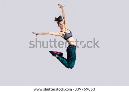 One happy attractive gorgeous young fit modern woman in aquamarine sportswear with ponytail working out, dancing, jumping with joy, full length, studio image on gray background - stock photo