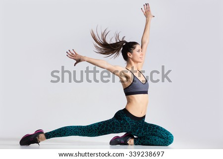 One happy attractive gorgeous young fit modern woman in blue sportswear with ponytail working out, dancing, in movement with her hair flying, full length, studio image on gray background - stock photo