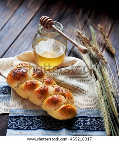 One home baked braided challah bread with poppy seeds for shabbat. One loaf served with honey, decorated with wheat. - stock photo