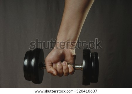 One human caucasian male hand holding one black iron dumbbell. Gray background. - stock photo