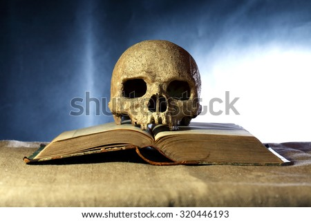 One human skull on old open book against dark background - stock photo