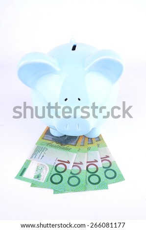 One hundred Australian dollar notes and a blue piggy bank - stock photo