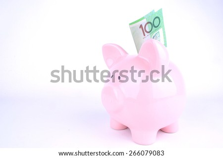 One hundred Australian dollar notes inserted into a pink piggy bank - stock photo