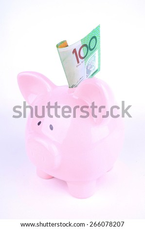 One hundred Australian dollar notes inserted into a pink piggy bank which has been shot in the studio. - stock photo
