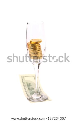 One hundred dollar banknote and golden coins in the glass. - stock photo
