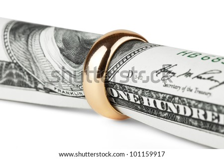 One hundred dollar bill in a gold wedding ring - stock photo