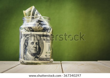 One hundred dollar bills in a glass jar. Green background - stock photo
