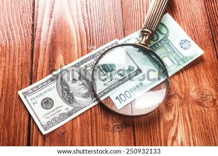 One hundred dollars and one hundred euros banknotes with vintage magnifying glass on them lying on wooden table - stock photo