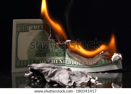 One hundred dollars in fire, burning dollar, ashes. Crisis - stock photo