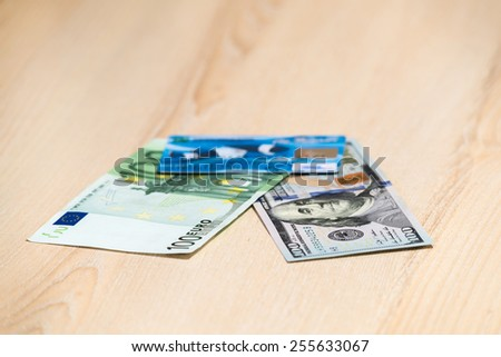 One hundred dollars, one hundred euros and a credit card lying on a wooden table beige - stock photo