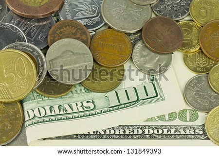 One hundred dollars under different coins - stock photo
