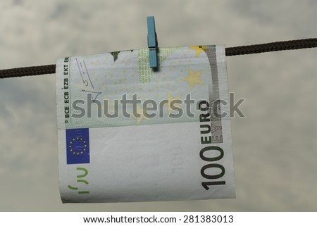 One hundred Euro banknote drying on string with cloudy  sky - stock photo