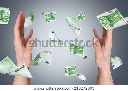 One hundred euro money banknotes flying and falling on young male hands. - stock photo