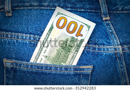 One hundred U. S. dollars bill sticking out of the back jeans pocket - stock photo