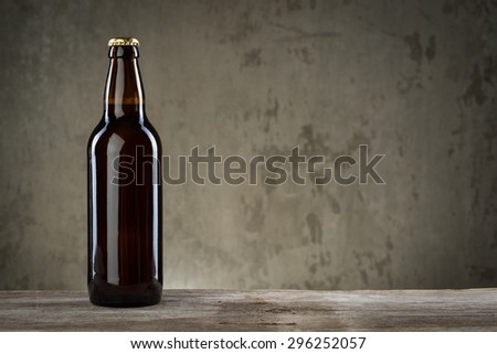 One ice cold beer bottles in a row over the grey concrete wall background - stock photo