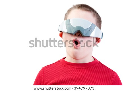 One impressed boy in red shirt wearing virtual reality glasses against a white background - stock photo